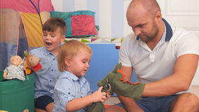 Glückliche Eltern und zwei kleine Jungen, die mit Marionetten spielen Lizenzfreie Stockfotografie