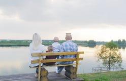 Glückliche Eltern und zwei kleine Kinder, die auf der Bank nahe dem See sitzen Stockfotos