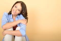Glückliche entspannte überzeugte junge Frau, die auf Boden sitzt Lizenzfreies Stockbild