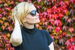 Glückliche entspannte Frau mit schwarzer Sonnenbrille und dem Hemd, die ihren Arm auf der Rückseite ihres Kopfes hält lizenzfreie stockfotos