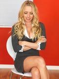 Glückliche entspannte Geschäftsfrau, die in einem Stuhl sitzt Lizenzfreie Stockfotos