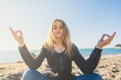Glückliche entspannte junge Frau, die in einer Yogahaltung am Strand meditiert lizenzfreie stockfotos