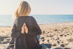 Glückliche entspannte junge Frau, die in einer Yogahaltung am Strand meditiert stockbild