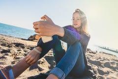 Glückliche entspannte junge Frau, die in einer Yogahaltung am Strand meditiert lizenzfreies stockbild