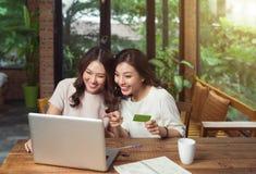 Glückliche entspannte junge Freundinnen, die durch das on-line-Einkaufen tun stockbilder