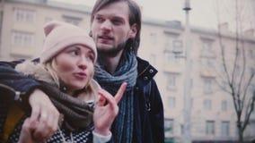 Glückliche entspannte junge romantische Paare der Zeitlupe gehen an einem Tag des verschneiten Winters zusammen umarmen, Händchen stock footage
