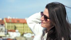 Glückliche entspannte touristische Frau, die sonniges warmes Wetter auf dem Damm lächelt genießt, Haar spielend stock video
