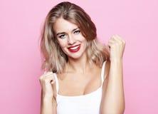 Glückliche erfolgreiche junge blonde Frau mit den angehobenen Händen schreiend und Erfolg über rosa Hintergrund feiernd Stockfoto