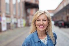 Glückliche erwachsene blonde Frau, die über die Straße lacht Lizenzfreie Stockfotografie