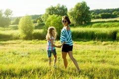 Glückliche erwachsene Frau, die draußen mit ihrem Tochterkindermädchen spielt Lizenzfreie Stockfotografie