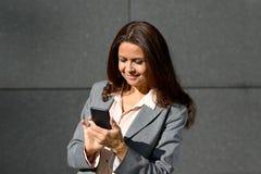 Glückliche erwachsene Frau, die Smartphone verwendet Lizenzfreie Stockfotografie