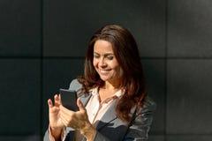 Glückliche erwachsene Frau, die Smartphone verwendet Stockfotos