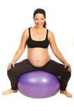 Glückliche erwartungsvolle Frau auf pilates Kugel Stockfotos