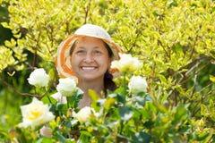 Glückliche fällige Frau in der Roseanlage Stockfotos