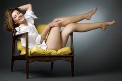 Glückliche fällige Frau, die auf Stuhl sich entspannt. Stockbilder