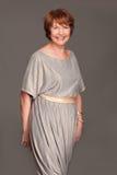 Glückliche fällige Frau im grauen Kleid Lizenzfreie Stockbilder