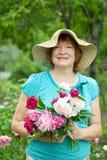 Glückliche fällige Frau mit Blumenstrauß Stockfotografie