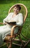 Glückliche fällige Frau mit Buch in Schwingstuhl Lizenzfreies Stockfoto