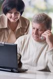 Glückliche fällige Paare, die an Laptop arbeiten Lizenzfreie Stockfotos