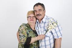 Glückliche fällige Paare mit Blumen lizenzfreie stockfotografie