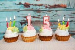 Glückliche fünfzehnte Geburtstagskuchen und rote Zahl 15 Kerzen auf blauem Weinlesehintergrund stockbilder