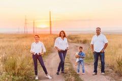 Glückliche Familie auf dem Gebiet bei Sonnenuntergang stockfoto