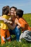 Glückliche Familie auf dem Gras Stockbild