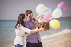 Glückliche Familie auf dem Strand mit Ballons und Korb Lizenzfreie Stockfotos