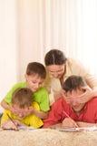 Glückliche Familie auf dem Teppich Lizenzfreie Stockfotografie