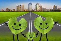 Glückliche Familie auf der grünen Straße mit Stadt. Klima-protecti Stockfotografie