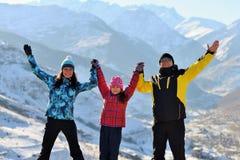Glückliche Familie auf eine Gebirgsoberseite auf Händen eines sonnigen Wintergriffs lizenzfreie stockfotos
