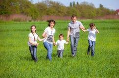 Glückliche Familie auf einem Gebiet Stockbilder