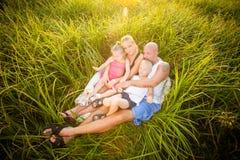 Glückliche Familie auf einer Wiese lizenzfreie stockbilder