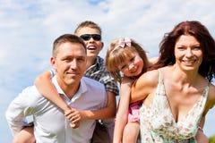 Glückliche Familie auf einer Wiese am Sommer Lizenzfreie Stockfotografie