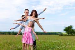 Glückliche Familie auf einer Wiese am Sommer Stockfotos