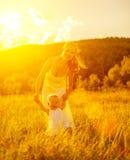 Glückliche Familie auf Naturmutter und -baby bei Sonnenuntergang Stockfotografie