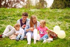 Glückliche Familie auf Picknick im geblühten Park, der auf Gras, Elternschaftsfreizeit in der Natur sitzt stockbild