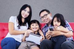 Glückliche Familie auf rotem Sofa, grauer Hintergrund Stockbilder
