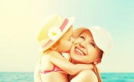 Glückliche Familie auf Strand Babytochter, die Mutter küsst Stockfotografie