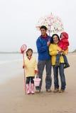 Glückliche Familie auf Strand mit Regenschirm Lizenzfreies Stockfoto