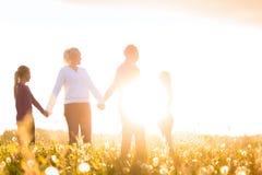 Glückliche Familie auf Wiese bei Sonnenuntergang Stockbild