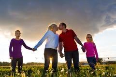 Glückliche Familie auf Wiese bei Sonnenuntergang Stockfotos