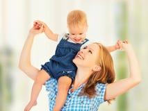 Glückliche Familie. Baby sitzt rittlings auf den Schultern der Mutter Stockbild
