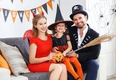Glückliche Familie in den Kostümen, die zu Hause zu Halloween fertig werden Lizenzfreie Stockbilder