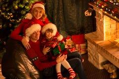 Glückliche Familie in den roten Hüten mit den Geschenken, die an sitzen Stockfotos