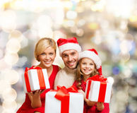Glückliche Familie in den Sankt-Helferhüten mit Geschenkboxen Lizenzfreie Stockfotos