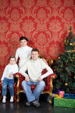 Glückliche Familie in den weißen Strickjacken und Jeans nähern sich Weihnachtsbaum Stockbilder