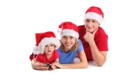 Glückliche Familie in den Weihnachtshüten lizenzfreie stockbilder