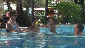 Glückliche Familie der Europäer, die mit einem Baby in einem Swimmingpool spielt junges Mädchen und die Frau, die das Babybällche stock footage