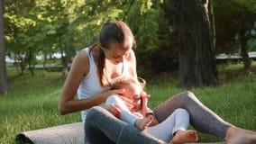 Glückliche Familie der jungen sportlichen Mutter und kleinen netten der Tochter, die Spaß draußen hat stock video